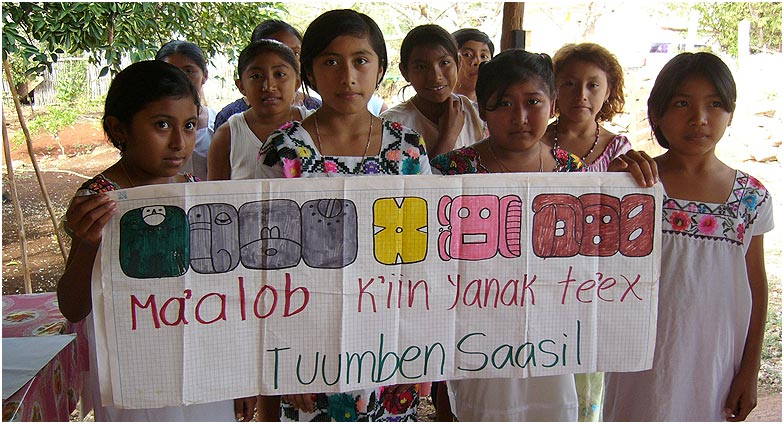 "Students of Tuumben Saasil, a hieroglyph class in the Yucatán village of Sisbicchén greet the crew with a banner. In hieroglyphs and alphabetic letters it proclaims ""A good day for you!""."